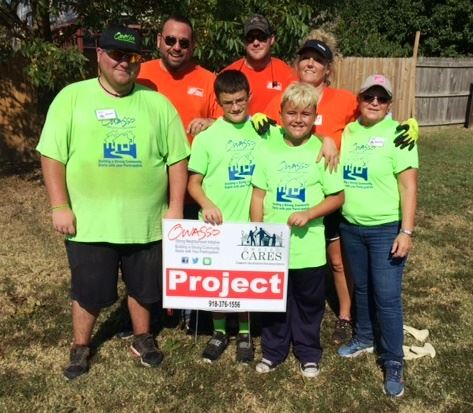Volunteers pose at project sign at Owasso CARES Day of Service
