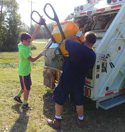 Volunteers unload wheelbarrow of tree limbs into refuse truck