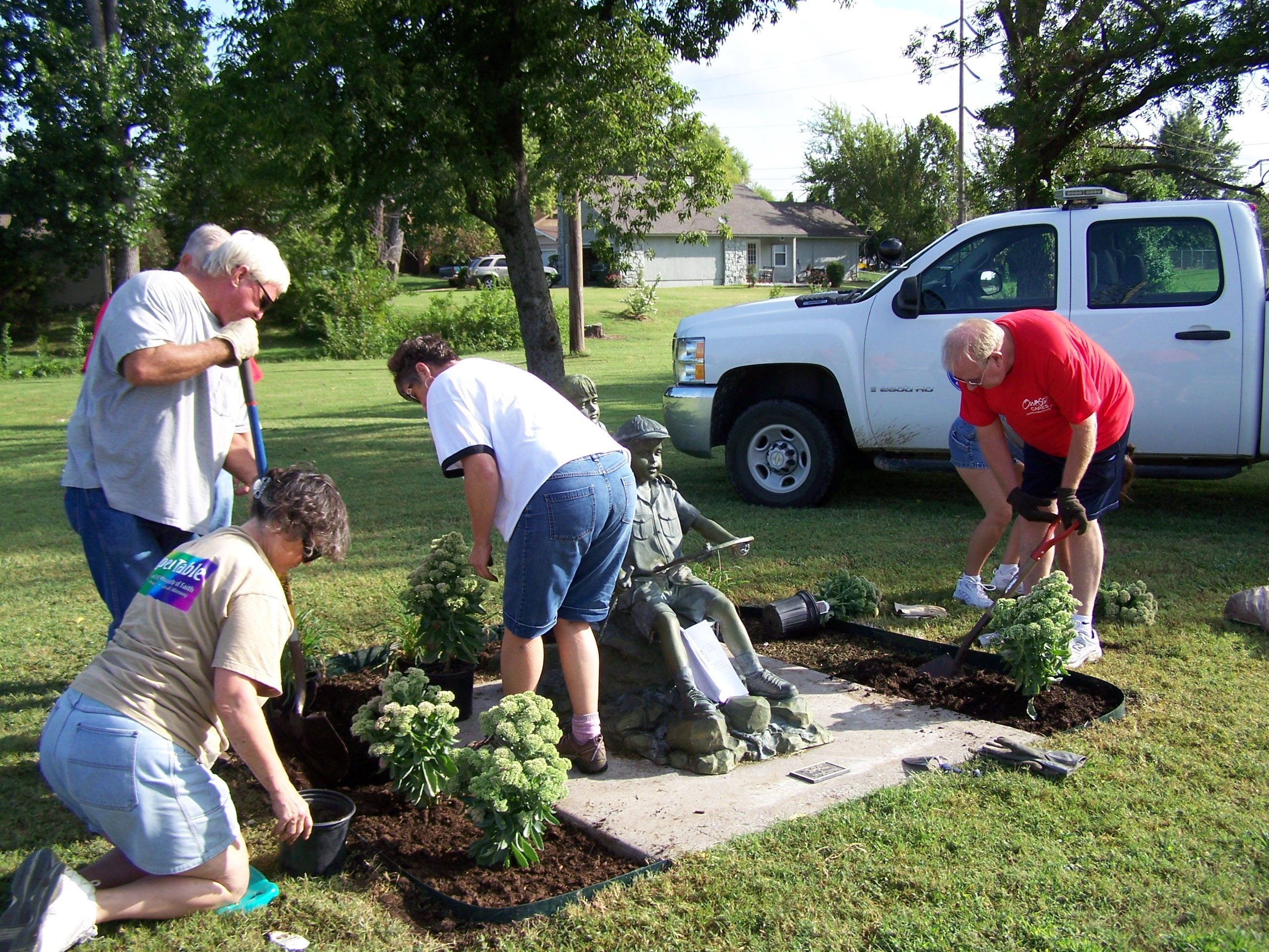 Volunteers plant flowers around statue at park