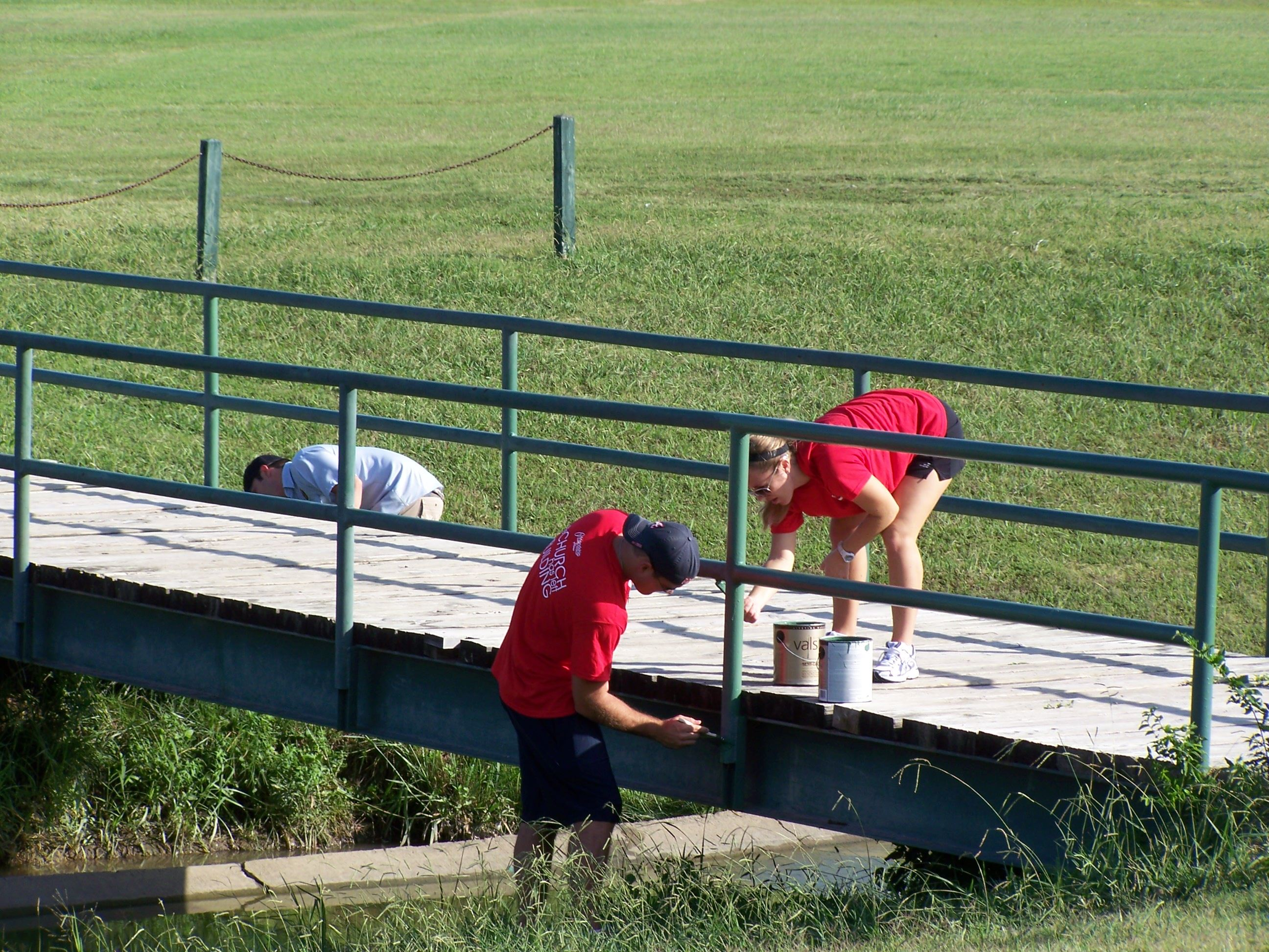 Volunteers paint park bridge railing
