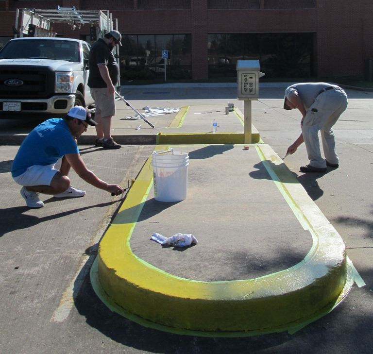 Volunteers painting Utility Payment curb at City Hall