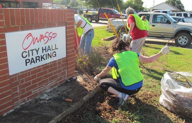 Volunteers clearing shrubs at City Hall parking lot entrance