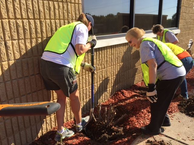 Volunteers clearing out shrubs at Community Center