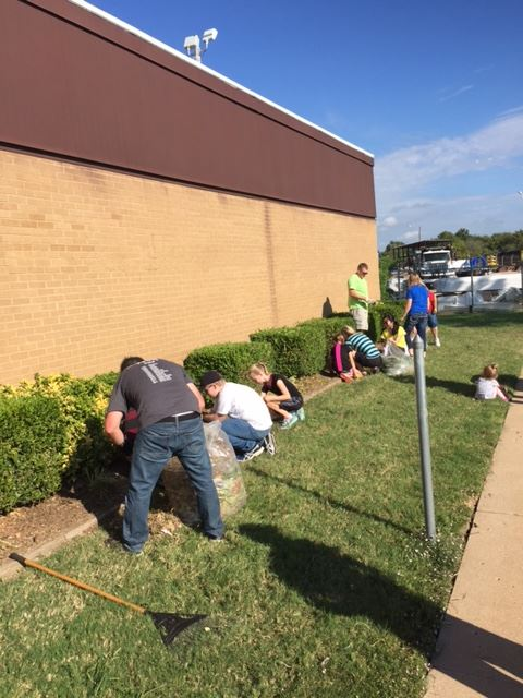 Volunteers trim shrubs and remove weeds at the Public Works facility