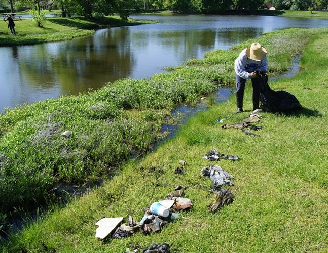 Volunteer picking up litter around neighborhood pond