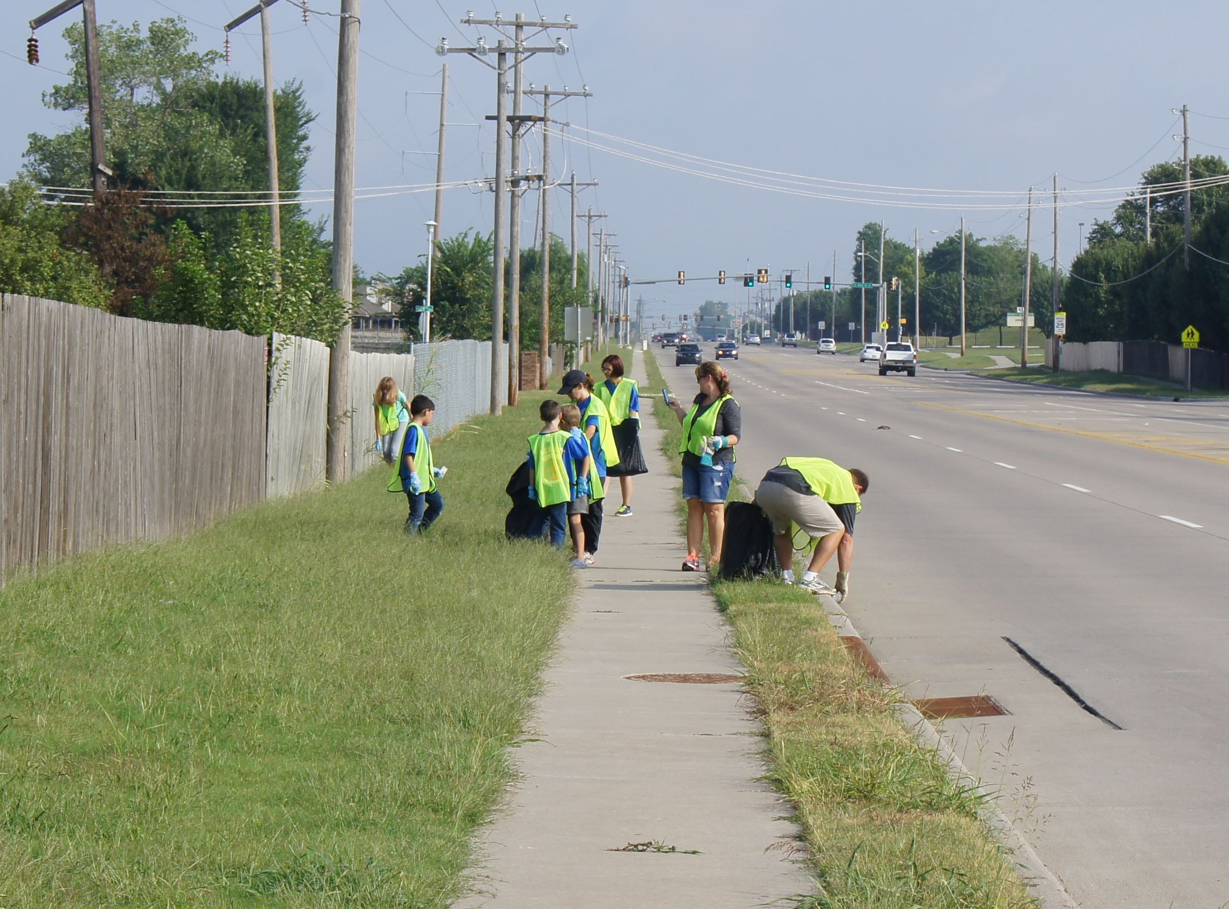 Volunteers picking up litter along sidewalk