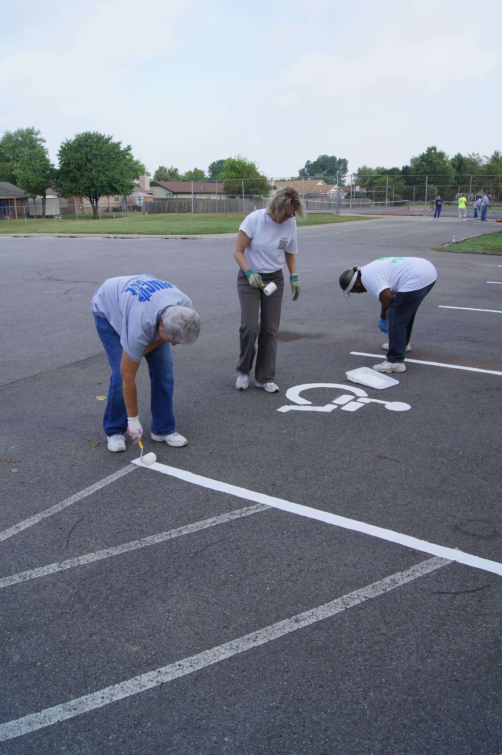 Volunteers painting handicap parking lines at park