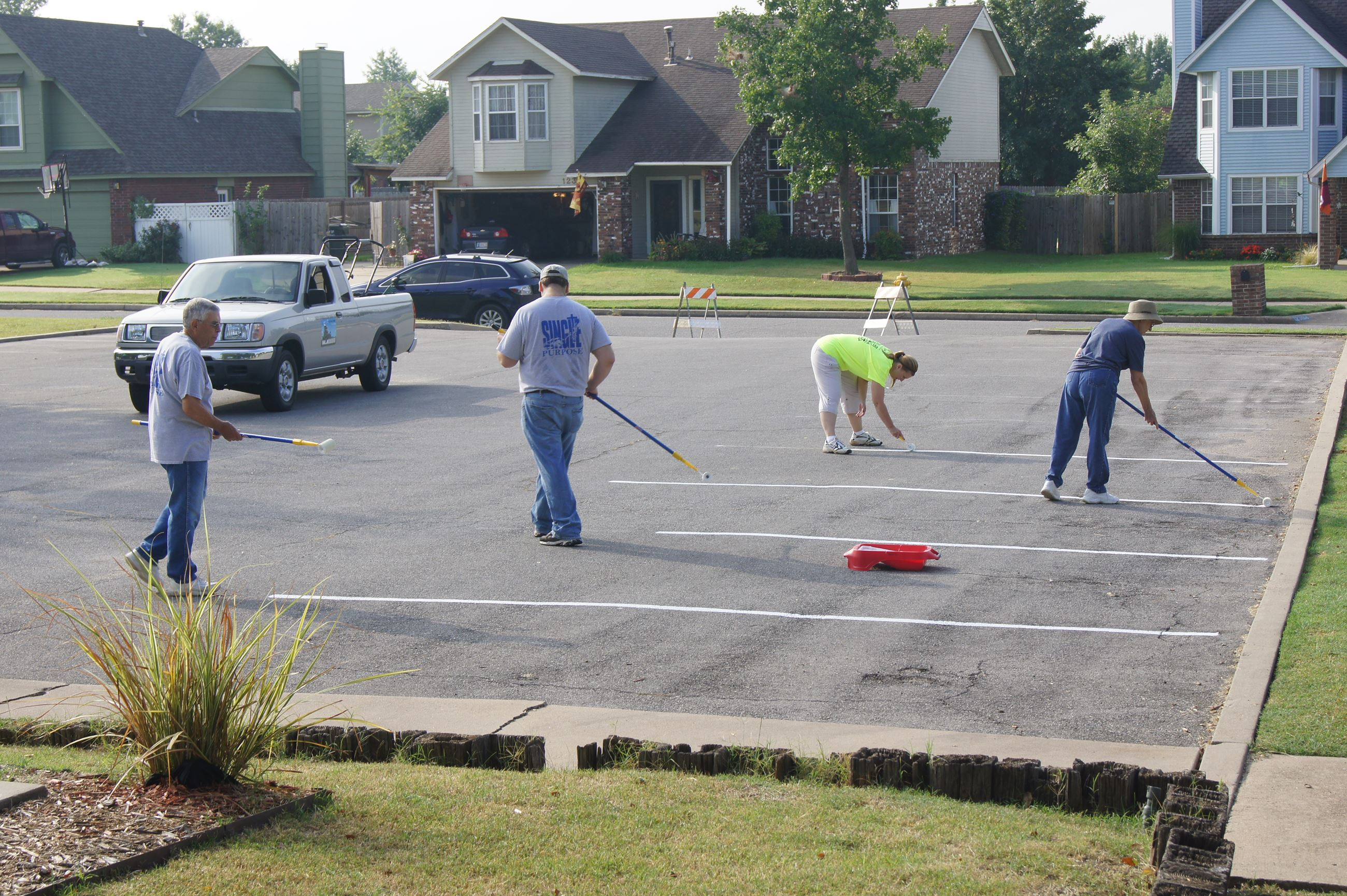 Volunteers painting parking lot stripes at park
