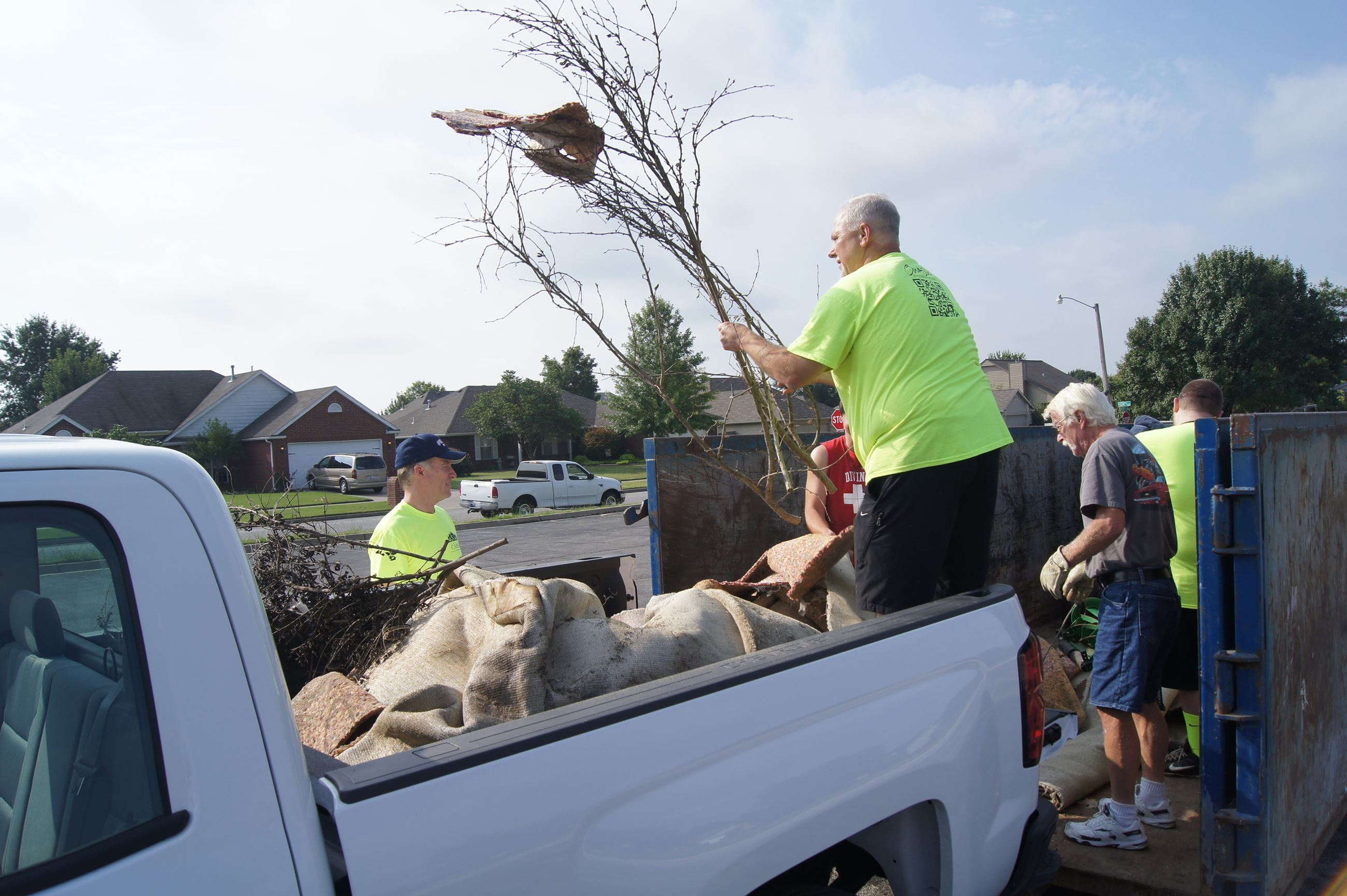 Volunteers unloading truck with debris into dumpster