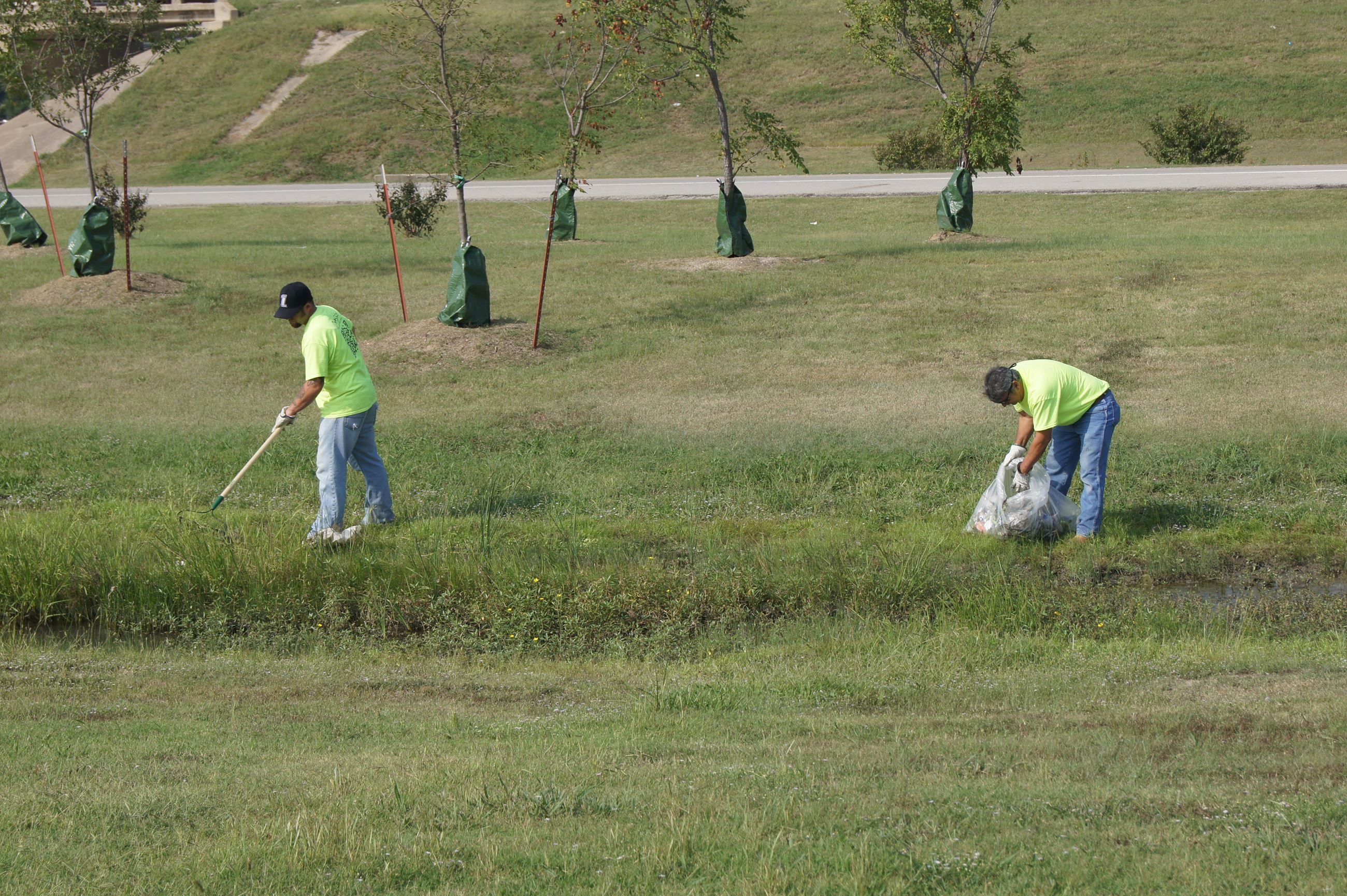 Volunteers picking up litter in drainage area